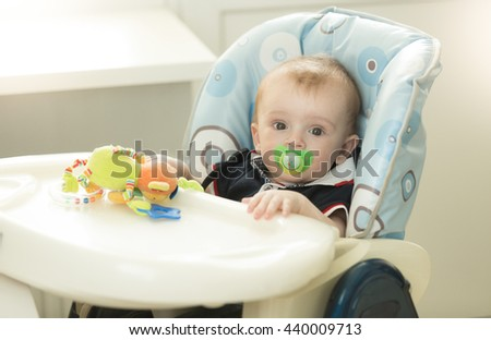 Portrait of adorable 9 months old baby boy with soother sitting in chair at kitchen - stock photo