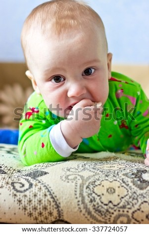 Portrait of adorable serious baby boy eating cabbage and looking at camera. Vertical image - stock photo
