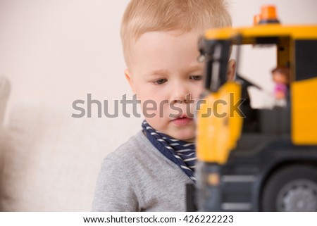 Portrait of adorable toddler boy sitting at the table playing with a big construction car at home.Little child with his toy car. Educative toys for children. Early learning and developing concept. - stock photo