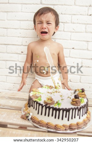 portrait of adorable toddler crying while playing smash cake - stock photo