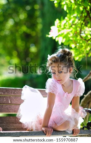 Portrait of adorable toddler girl wearing ballet costume in beautiful garden background - stock photo
