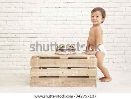 portrait of adorable toddler smiling with cake on wooden box - stock photo