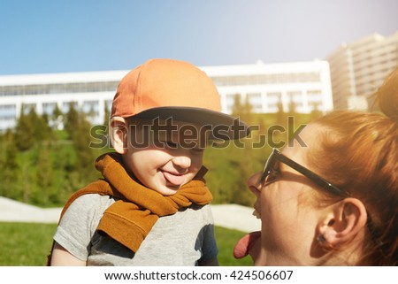 Portrait of adorable two-year old toddler wearing stylish clothes and cap showing tongue to her young mother. Redhead woman holding her son against green park background. Film effect, flare sun  - stock photo