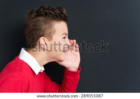 Portrait of adorable young boy sharing a secret at the black chalkboard in classroom. - stock photo