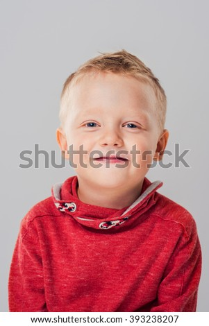 Portrait of adorable young happy boy looking at camera. Photo of a smiling boy in red pullover over gray background - stock photo