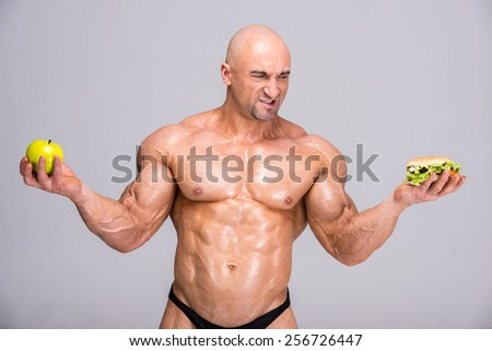 Portrait of adult bodybuilder is holding apple in his hand and hot dog. Healthy lifestyle. - stock photo