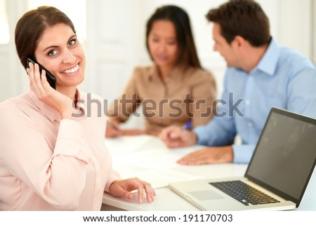 Portrait of adult businesswoman talking on her cellphone while smiling at you and sitting with male and female coworker on office desk - stock photo