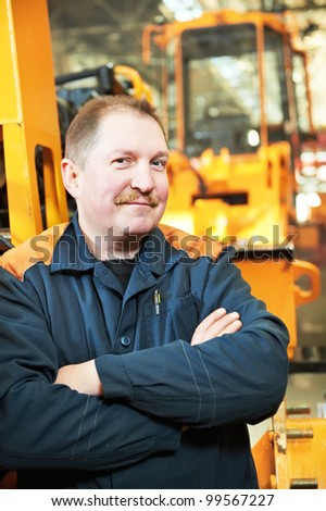 Portrait of adult experienced industrial worker over heavy industry machinery production line manufacturing workshop - stock photo