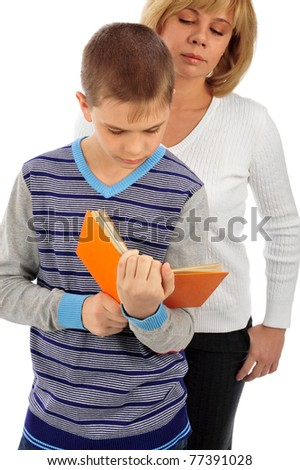 Portrait of adult woman watching as her son doing homework - stock photo