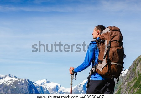 portrait of adventure man with backpack in the mountains - stock photo