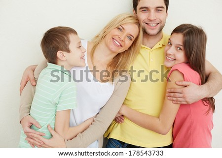Portrait of affectionate family of four embracing - stock photo