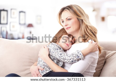 Portrait of affectionate mother hugging her daughter while sitting on sofa at home.  - stock photo