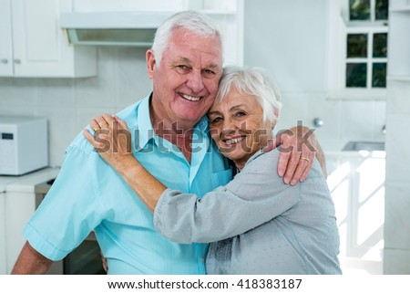 Portrait of affectionate senior couple embracing at home - stock photo