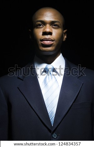 Portrait of African American businessman in darkness - stock photo