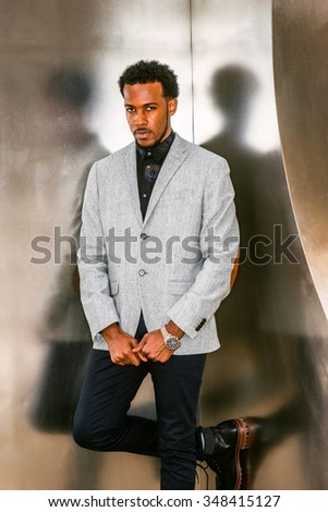 Portrait of African American Businessman in New York. Wearing gray patterned blazer, black pants, wristwatch, black professional with beard standing against silver metal wall. Instagram filtered look. - stock photo