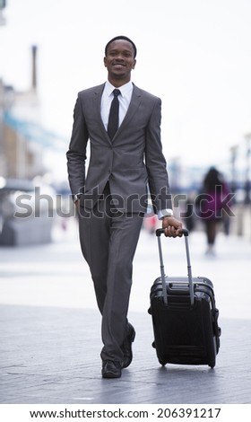 Portrait of African American businessman smiling and pulling suitcase - stock photo