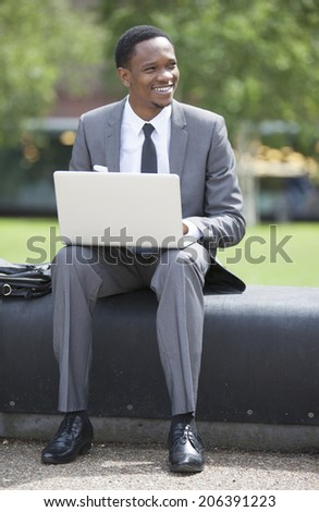 Portrait of African American Businessman working on a laptop outdoors - stock photo