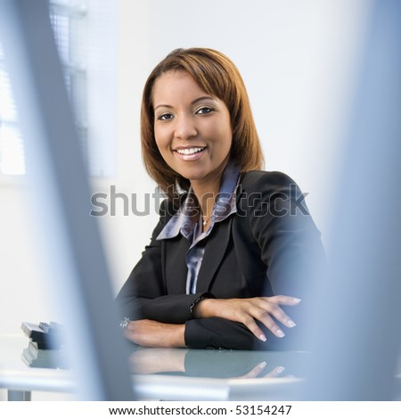 Portrait of African American businesswoman sitting at office desk smiling. - stock photo