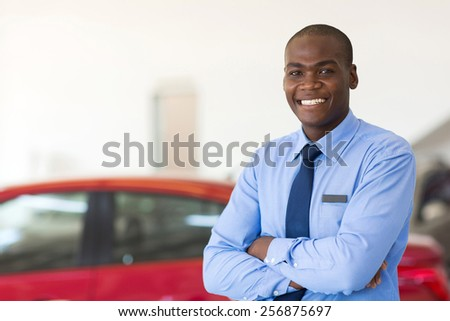 portrait of african american car sales consultant with arms folded in showroom - stock photo