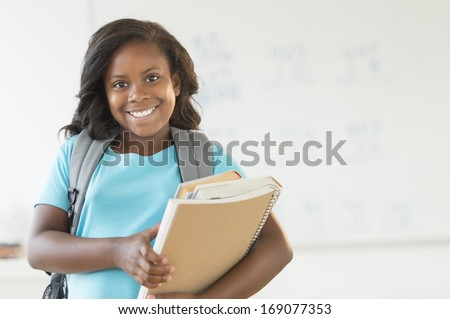 Portrait of African American schoolgirl carrying books and backpack in classroom - stock photo