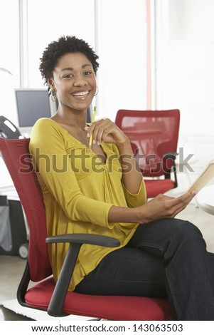 Portrait of African American woman with pencil and notepad sitting on office chair - stock photo