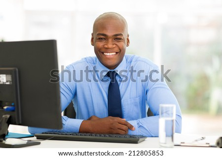 portrait of african businessman sitting in office - stock photo