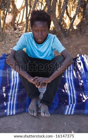 Portrait of African child in the hut, on the blanket, location Mmankodi village, Botswana - stock photo