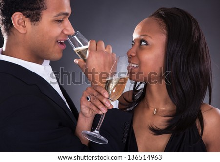 Portrait Of African Couple Enjoying Champagne Drink Over Grey Background - stock photo