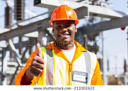 portrait of african electrician with thumb up at substation - stock photo