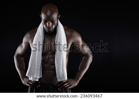 Portrait of african male athlete after workout against black background. Shirtless muscular man with a towel looking down with his hands. - stock photo