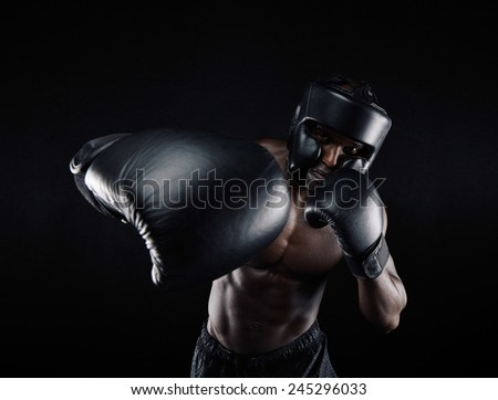 Portrait of african male practicing boxing against black background. Male boxer throwing a punch in front. Young sportsman training boxing. - stock photo