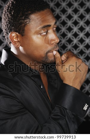 Portrait of African man with hand up to mouth - stock photo
