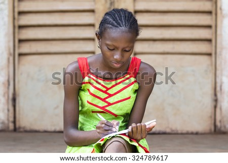 Portrait of African School Girl Writing outside her classroom. A beautiful girl writing in the school of Bamako, Mali. Front view of a black proud child wearing a green / red dress writing down notes. - stock photo