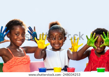 Portrait of African threesome showing painted hands.Isolated against light background. - stock photo