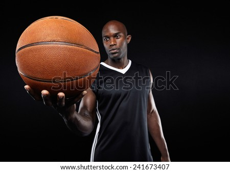 Portrait of african young basketball player with a ball against black background. Focus on basketball. - stock photo