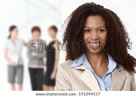 Portrait of afro businesswoman at office, colleagues in background. - stock photo