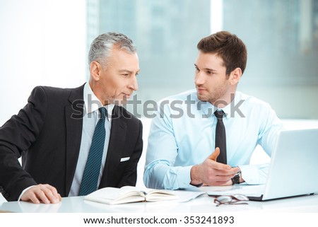 Portrait of aged and young businessmen in office with big window. Businessmen having meeting and transfering knowledge - stock photo