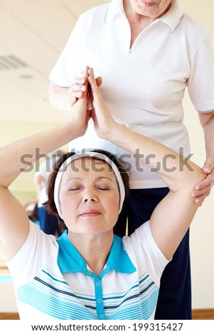 Portrait of aged female doing yoga exercise with her sports instructor in gym  - stock photo