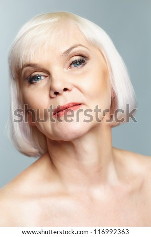 Portrait of aged female posing in front of camera - stock photo