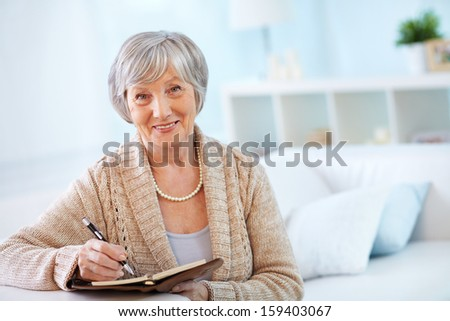 Portrait of aged female with notepad looking at camera with smile - stock photo
