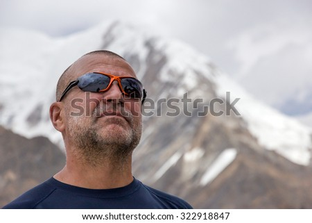 Portrait of Aged Mountain Climber Face of Elder Man in Protective Sunglasses Bearded Unshaven Looking Up on Way to Summit with Mountain Landscape on Background - stock photo