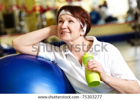 Portrait of aged woman with bottle of water by blue ball - stock photo