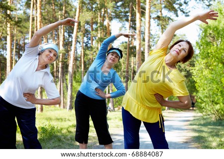 Portrait of aged women with their arms raised while doing physical exercise - stock photo