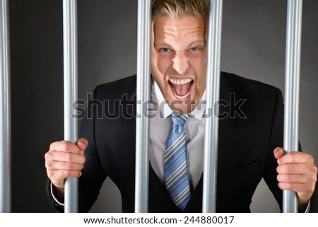 Portrait Of Aggressive Businessman Standing Behind Bars - stock photo
