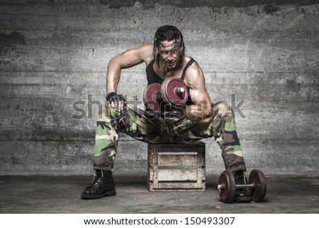portrait of aggressive muscle man lifting weights on wall background - stock photo