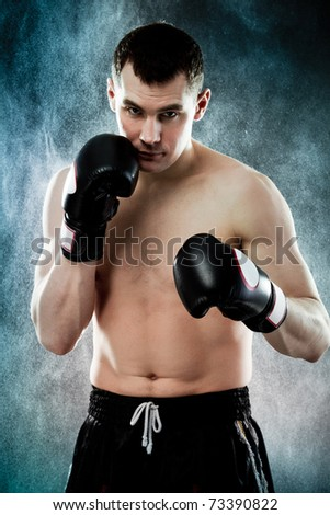 Portrait of agressive male boxer with splashes of water on background - stock photo