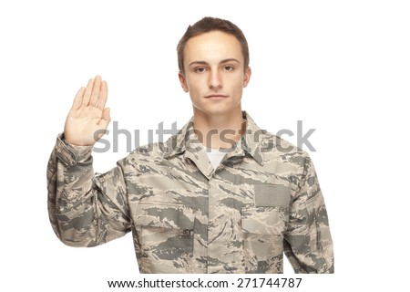 Portrait of air force airman with hand raised for oath of enlistment against white background - stock photo