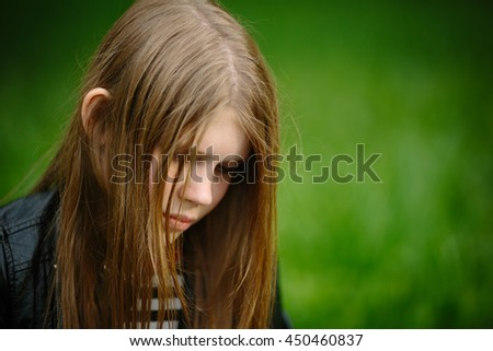 Portrait of alone thoughtful sadness girl is sad on the green background - stock photo