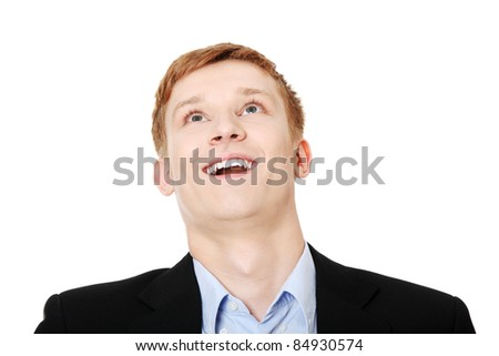 Portrait of amazed happy businessman looking up with mouth open against white background - stock photo