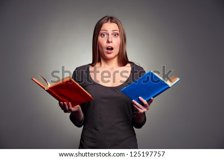 portrait of amazed woman with books over grey background - stock photo